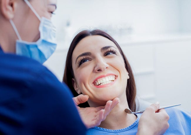 A female patient smiles excitedly as someone finishes performing teeth whitening work on her mouth.