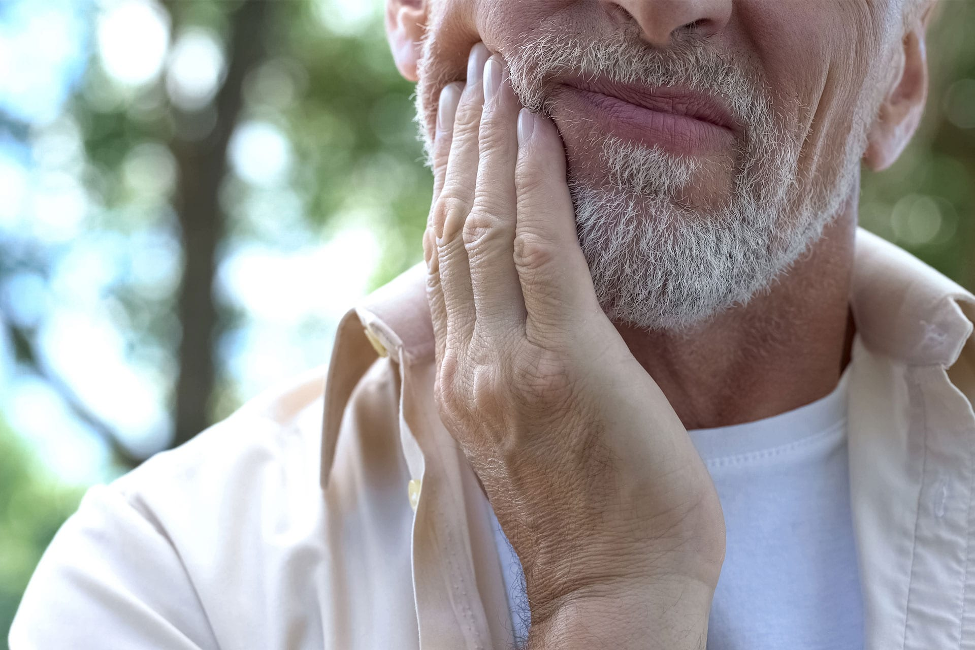 Man with a toothache touches his cheek.